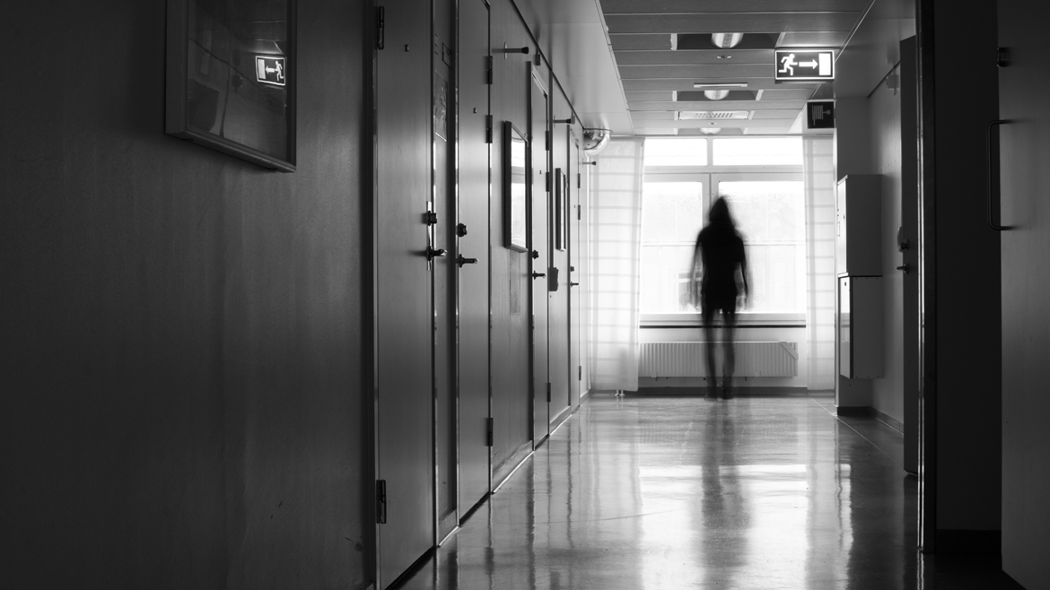 Unrecognizable silhouette of person in blurred motion in front of window in a hostpital corridor.